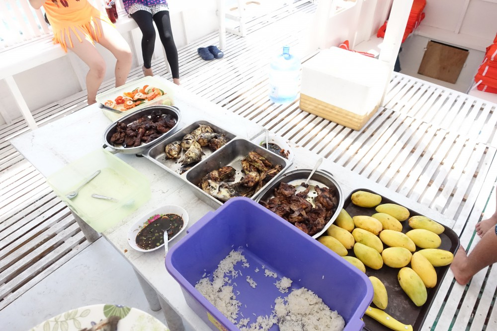 船の上で食べる食事。ご飯、チキン、豚肉、サラダ、魚、マンゴーなどなど。